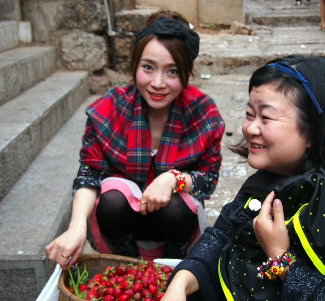Young girls shop for strawberries.
