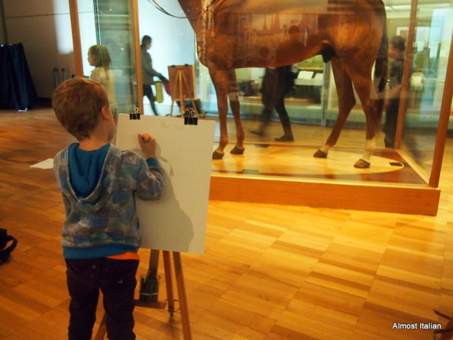 a young boy stands at his easel, sketching xx enca