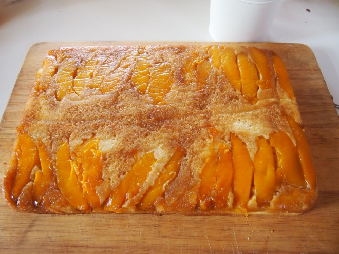 Upside down mango slab cake emerges from it's tin.