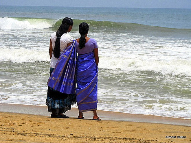 Beautiful girls stand on the edge of the Arabian Sea.
