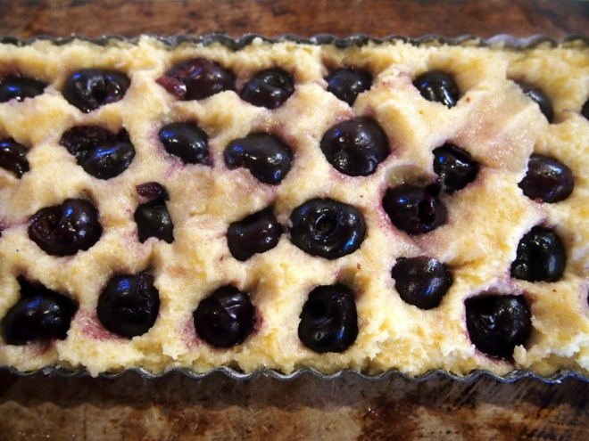 Press whole cherries into the almond batter.