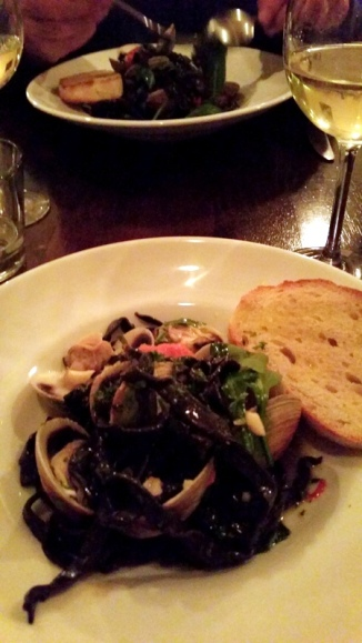 A tangle of squid ink pasta and a generous serving of little neck clams.
