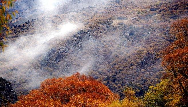 Long white cloud moves across Autumn hills