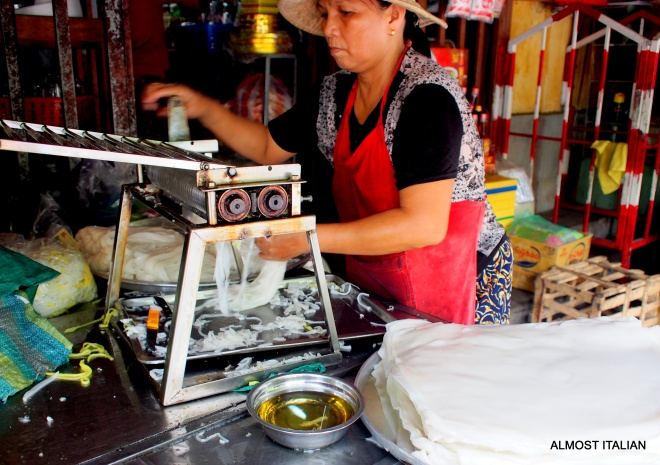 Market lady making fresh Bánh phở noodles.