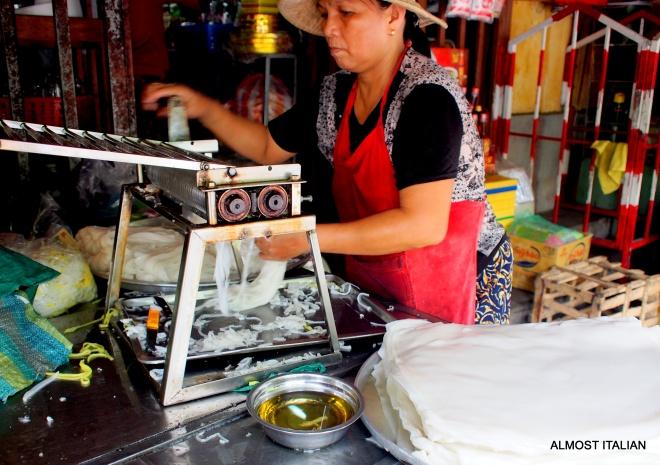 Market lady making fresh Bánh phở noodles.