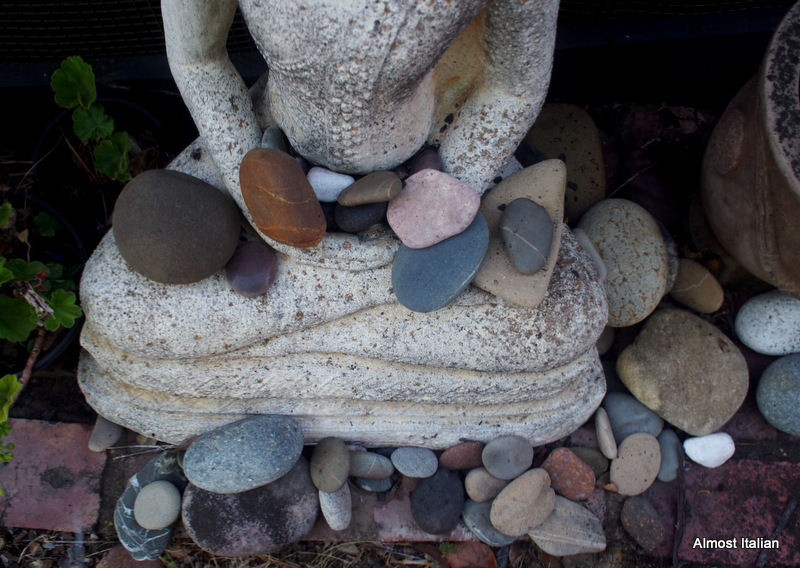 Buddha lost the pointy top of his head. Now he is a rock collector and pool guard.